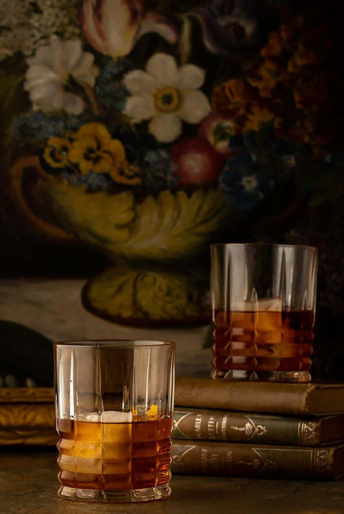 2 cocktails on a table in front of a dark floral print.