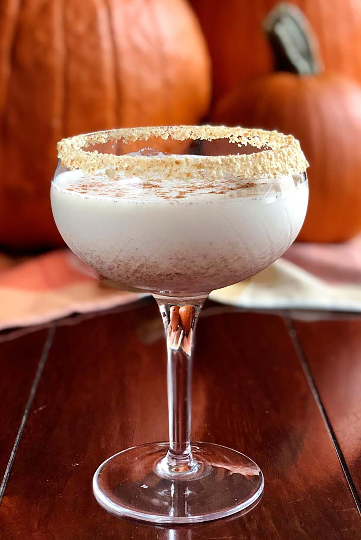 A cocktail in front of pumpkins, garnished with crumbs.