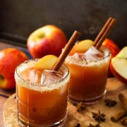 2 cocktails garnished with cinnamon sticks, apple slices and sugar rims, surrounded by a few apples and spices on the base.