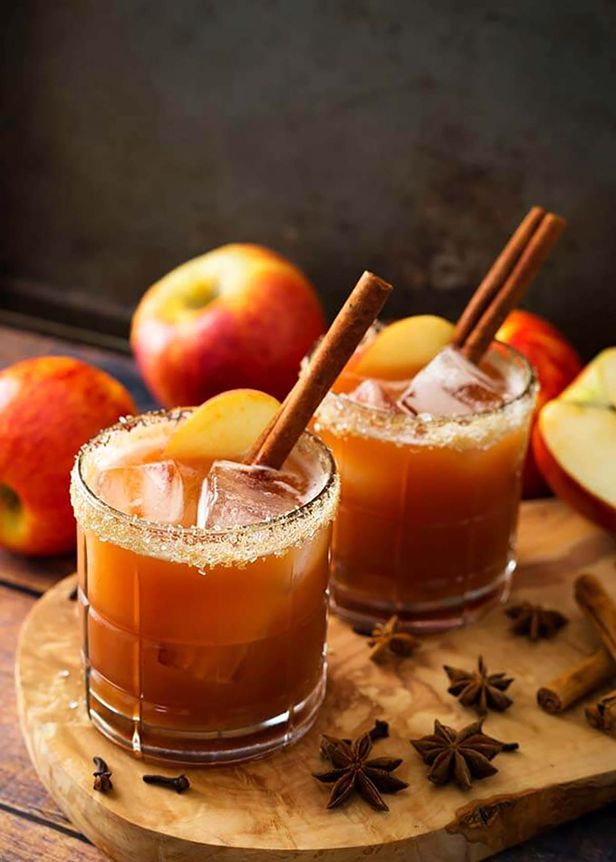 2 apple cocktails garnished with cinnamon sticks, apple slices and sugar rims.
