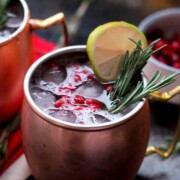 A cocktail in a mug, garnished with rosemary, a lemon and pomegranate seeds beside another cocktail and bowl of more seeds.