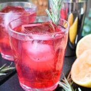 A cranberry cocktail garnished with rosemary beside 2 lemons and another cocktail in the background.