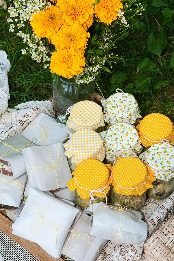 Fabric-topped pasta salad jars and small wrapped sandwiches in a tray on grass, next to a bouquet of marigolds.