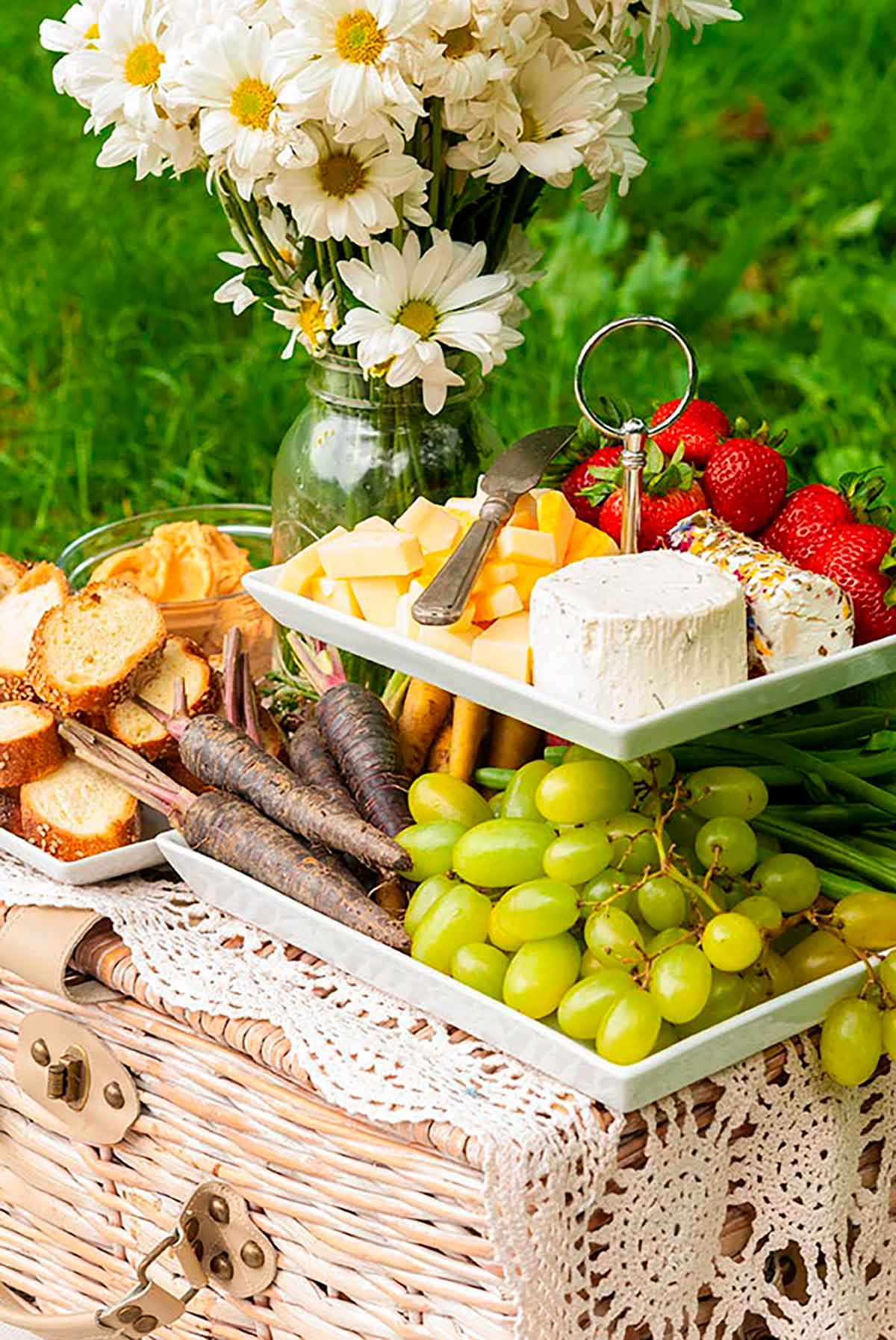 A 2 tiered plate with fruits, vegetables, cheese and bread, placed on a picnic basket, beside a jar of daisies on grass.
