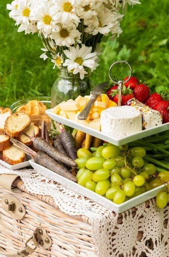 A 2 tiered plate with fruits, vegetables, cheese and bread, placed on a picnic basket, beside a jar of daisies.