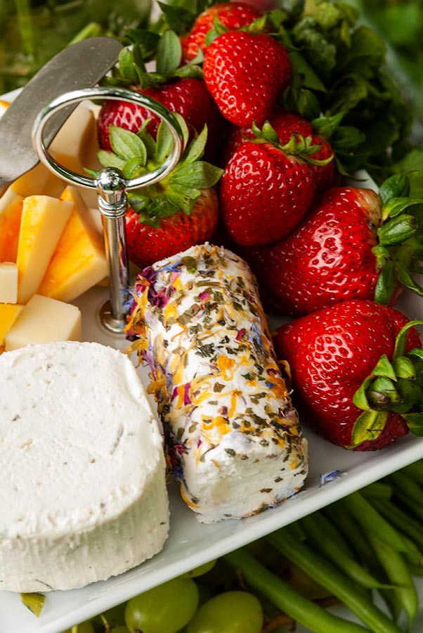 An assortment of fruits and flower-covered cheese on a plate.