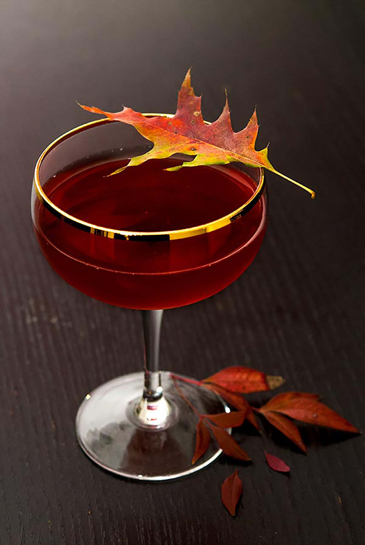 A red cocktail garnished with a colorful, autumn leaf on a dark wood table with leaves at its base.