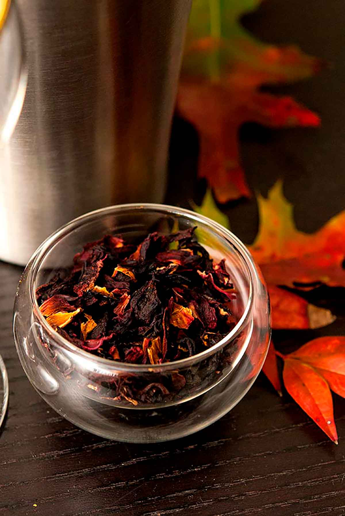 A small bowl of hibiscus flowers on a table with a few autumn leaves, in front of a cocktail shaker.