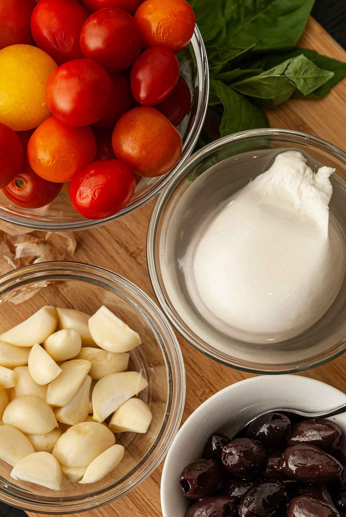 Small bowls on a wooden board with mozzarella, tomatoes, olives and garlic.