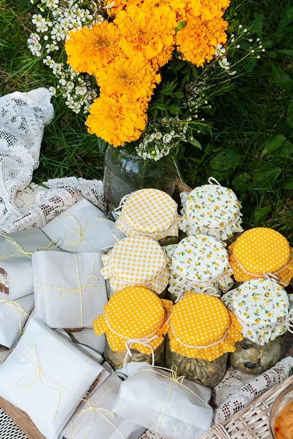 Fabric-covered jars of pasta salad and wrapped sandwiches in a lace-lined tray with a bouquet of marigold flowers.