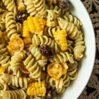 A bowl of pesto pasta salad with corn, olives, cherry tomatoes and mozzarella.