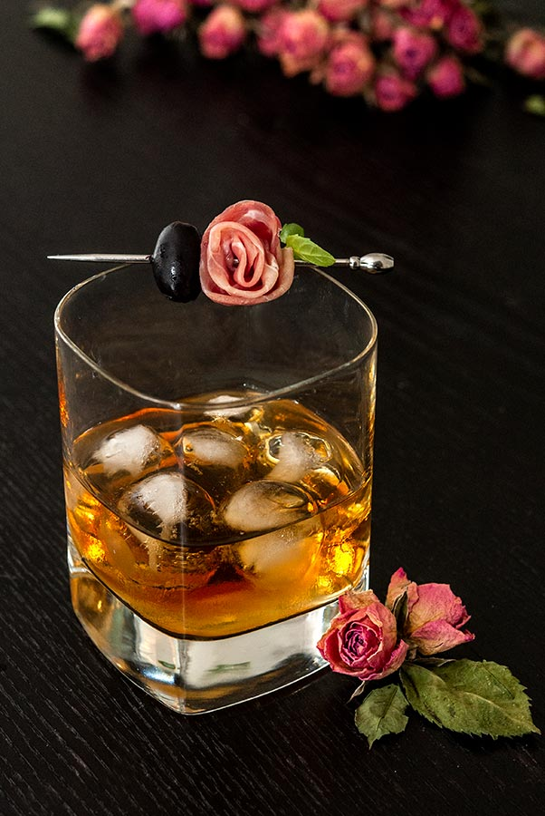 A whisky cocktail on a black table, surrounded by pink roses, garnished with a prosciutto rose garnish and olive.