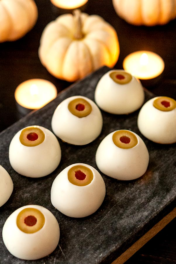 8 upside-down deviled eggs that look like eyeballs on a slate in front of candles and white pumpkins.