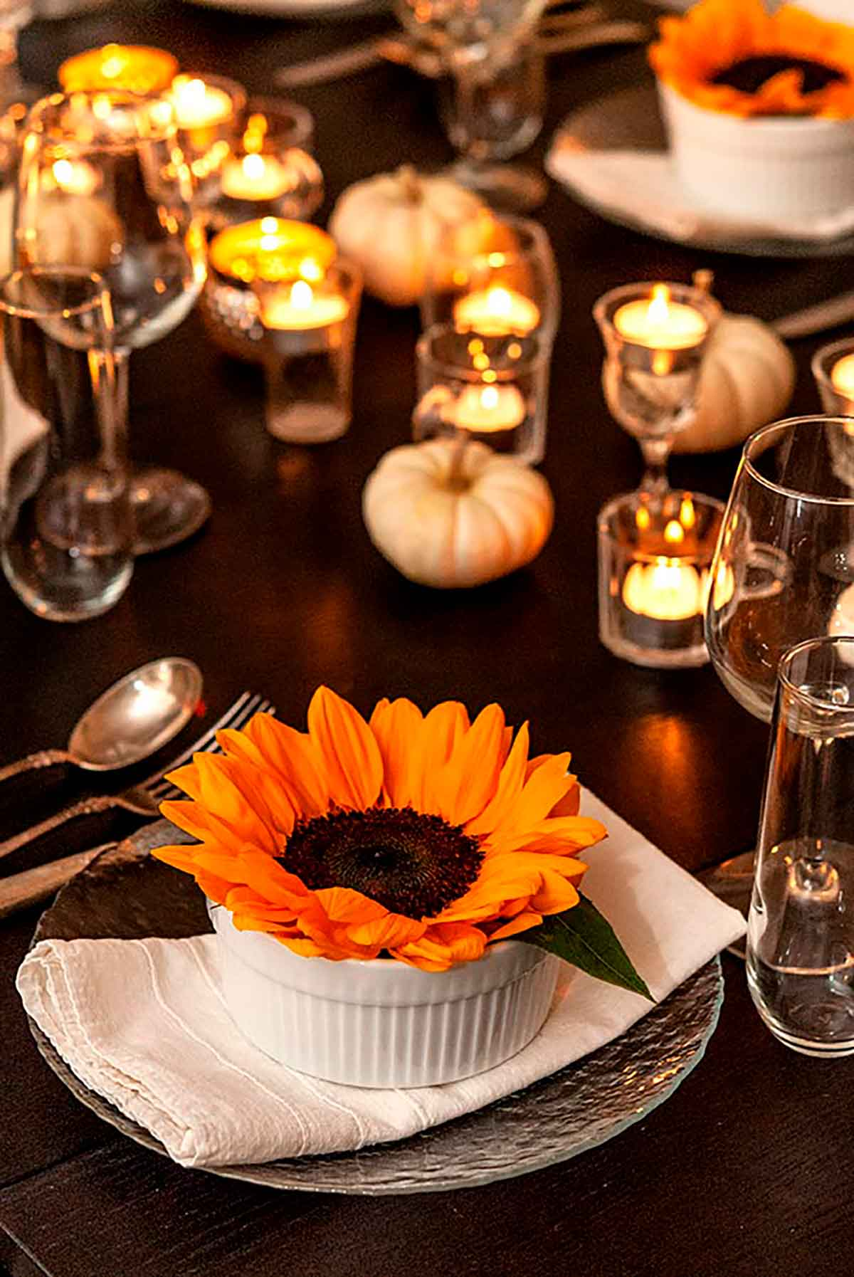 A sunflower in a soup bowl on a set dinner table, decorated with tea lights and small, white pumpkins.