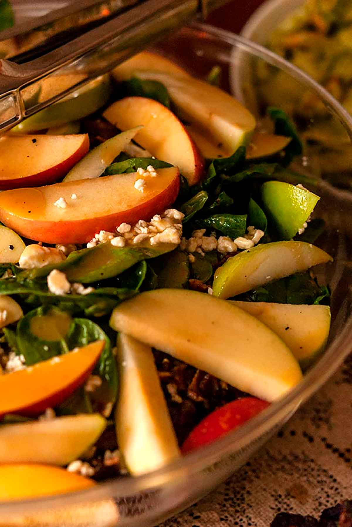 A large bowl of salad with apples, sprinkled with cheese.