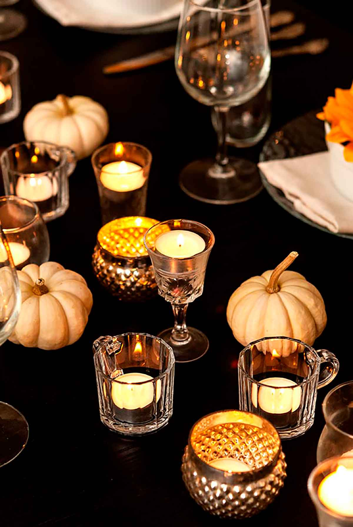 Tea lights in cordial cups and small white pumpkins on a dinner table.