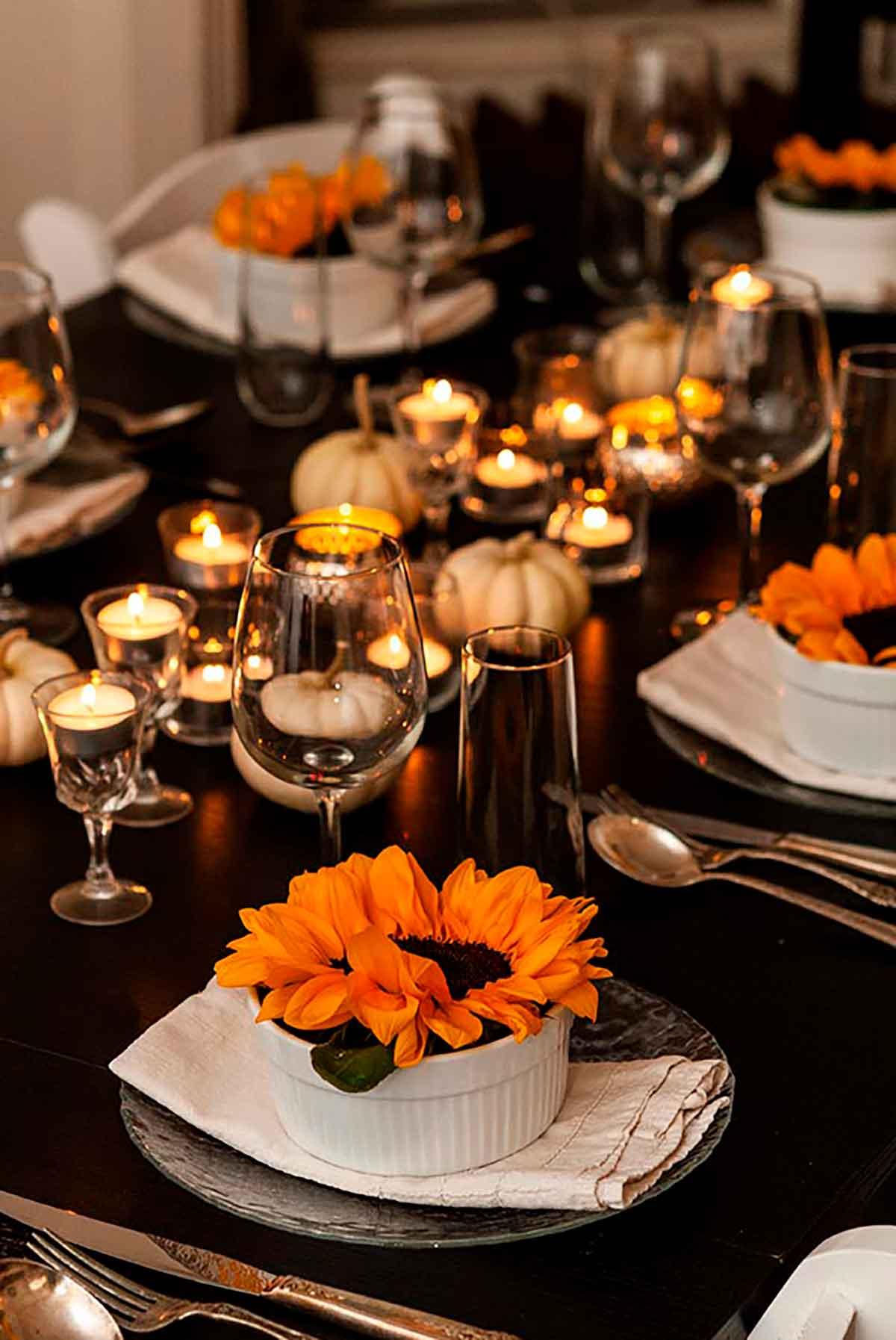 A dinner table set with tea lights, small white pumpkins, glassware and soup bowls with sunflowers inside.