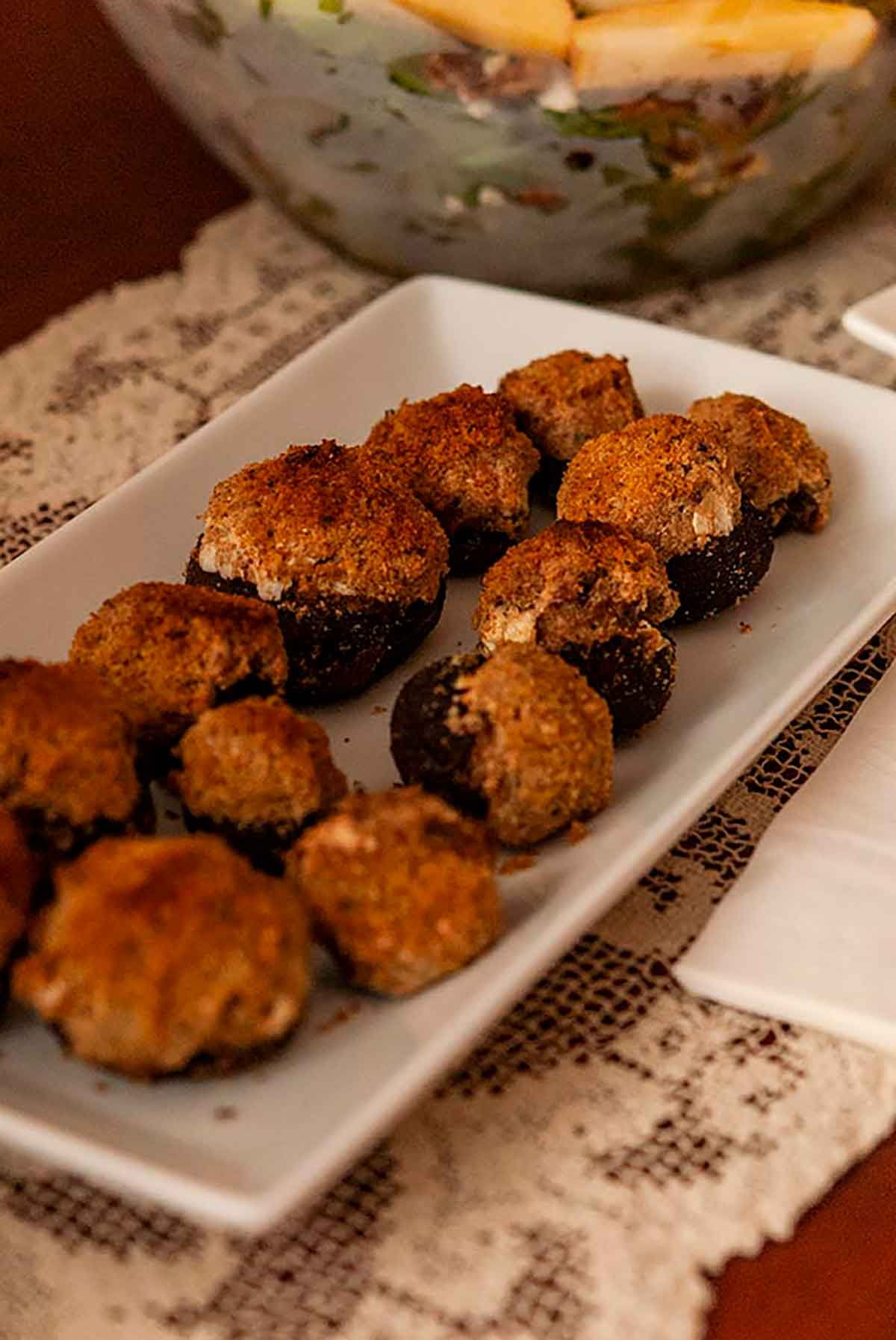 A plate of stuffed mushrooms on a table with an old, lace tablecloth.