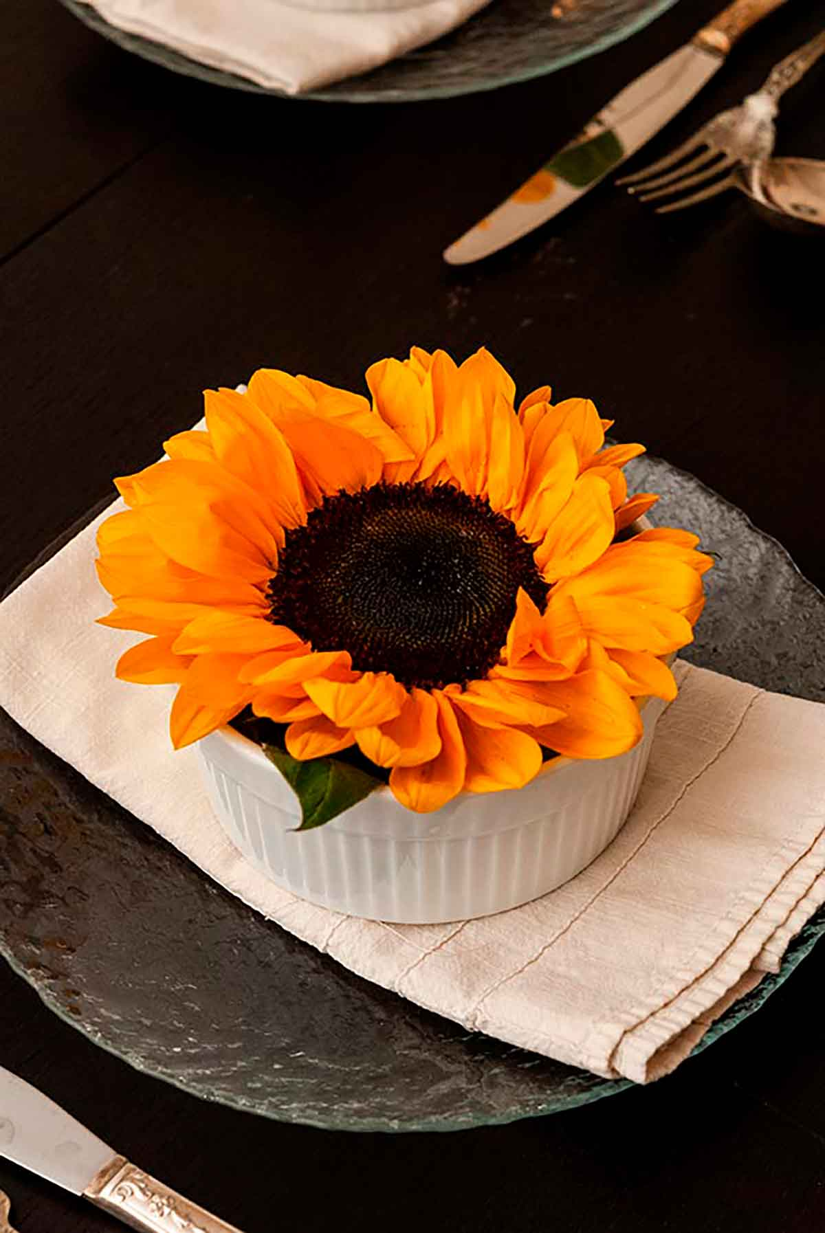 A sunflower in a soup bowl, on top of a folded napkin, on top of a plate on a table.