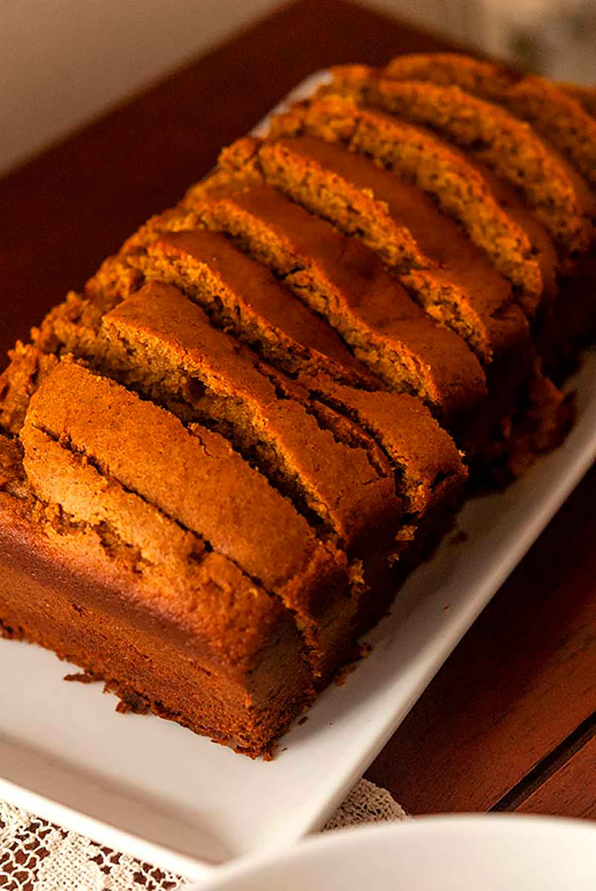 A sliced loaf of pumpkin bread on a plate.