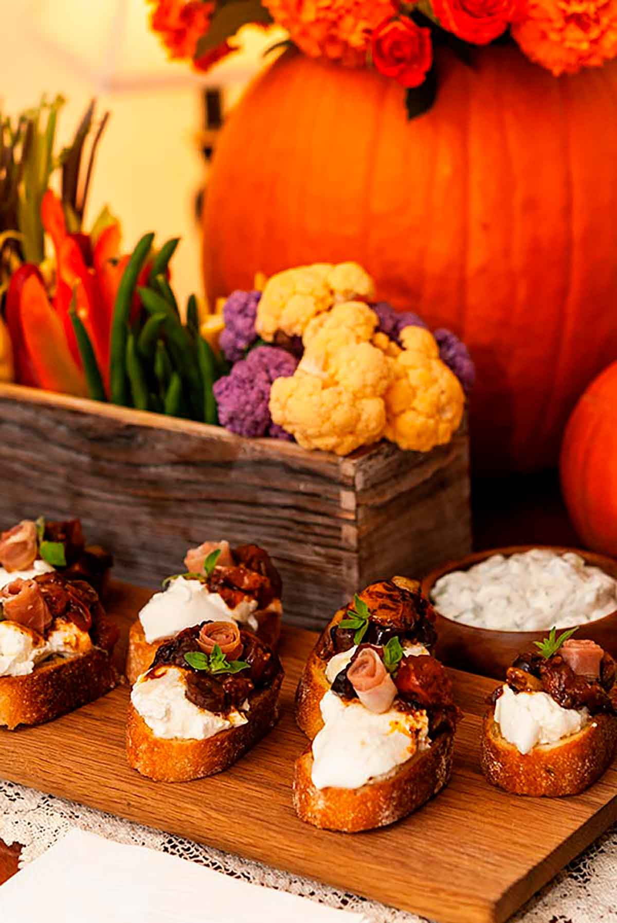 7 bruschetta, garnished with prosciutto roses on a wooden board and a flower-box crudités in front of a pumpkin.