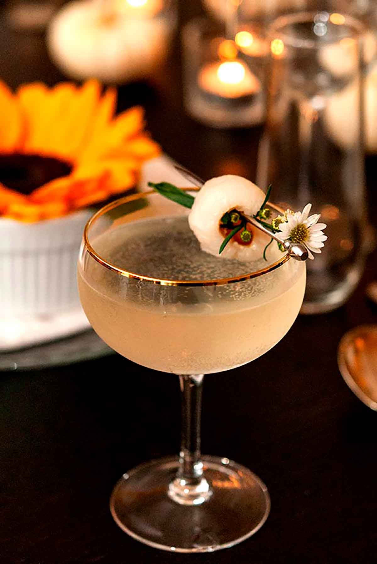 A cocktail, garnished with a lychee and small daisy, on a set dinner table with sunflowers, glasses and candles.
