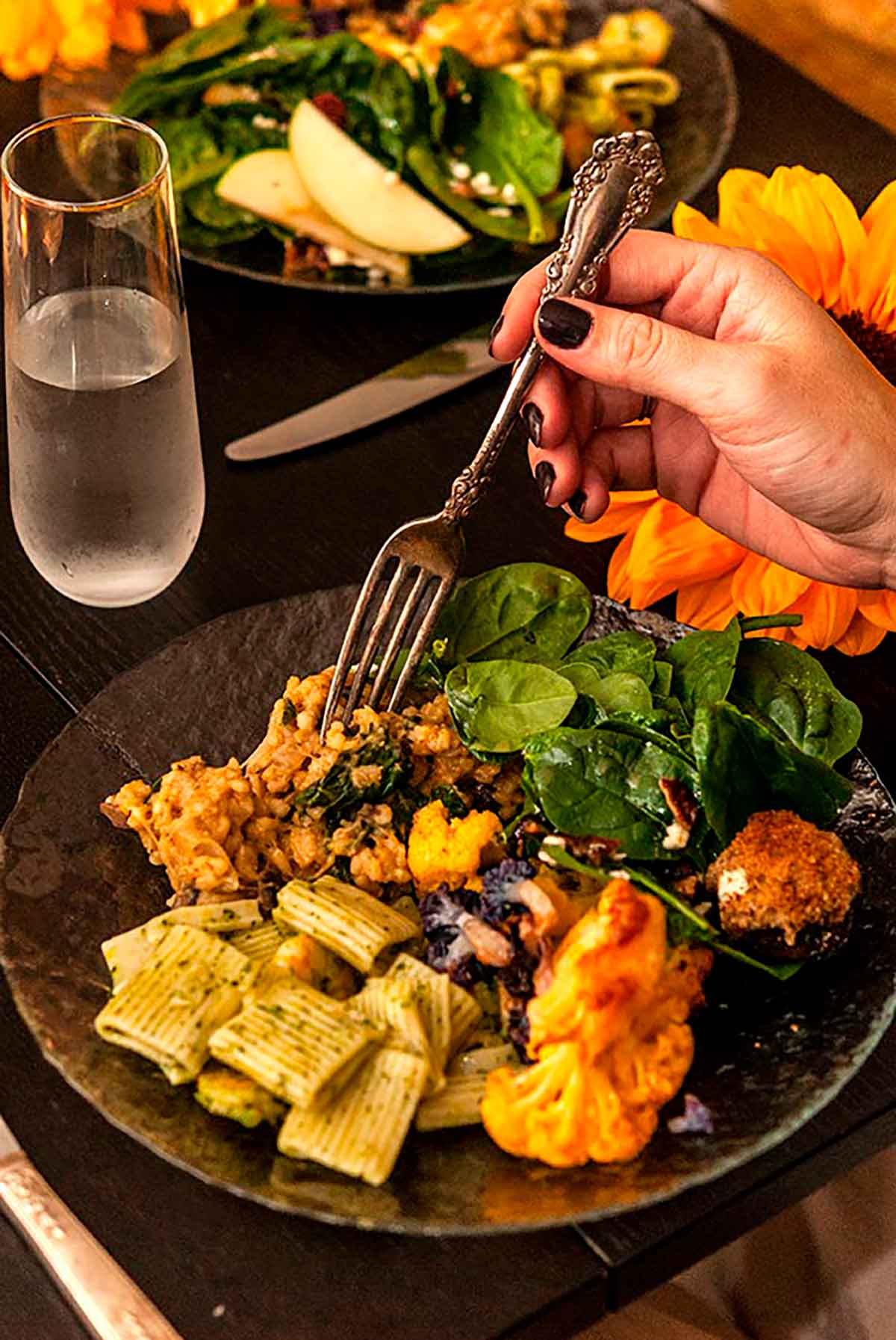 A hand holding an antique fork above a plate full of food with a sunflower and other plates of food in the background.