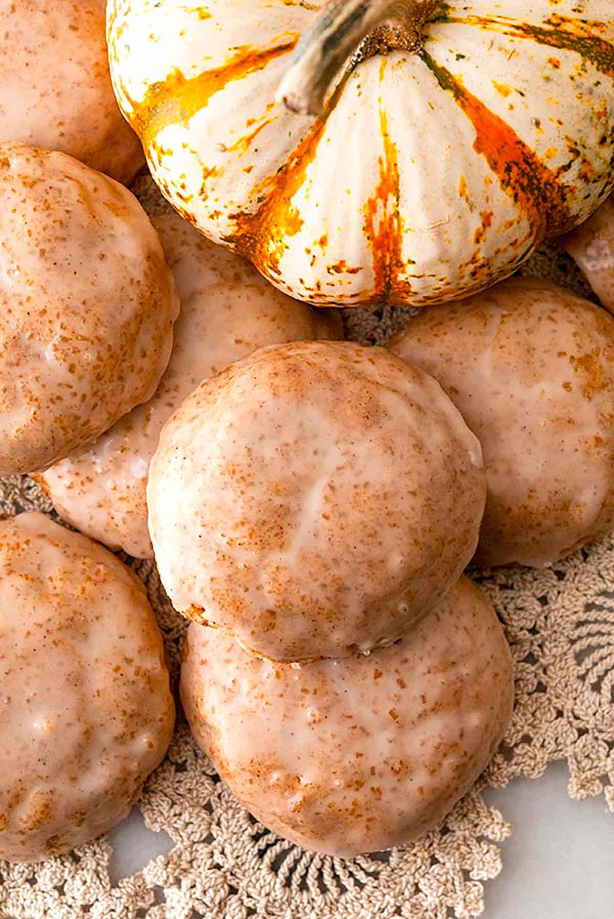 7 glazed cookies on lace, beside a pumpkin gourd.