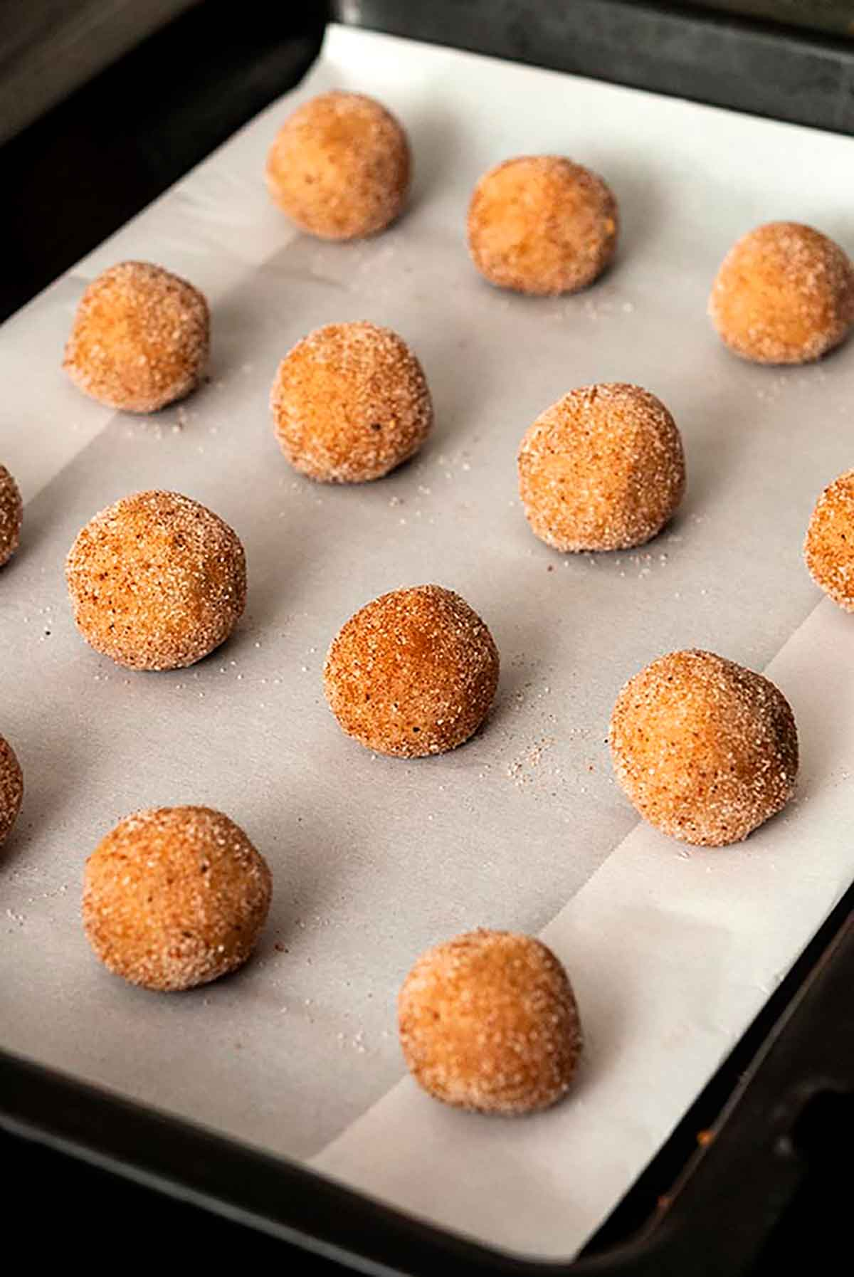 16 balls of sugar-coated dough on a parchment-lined baking pan.