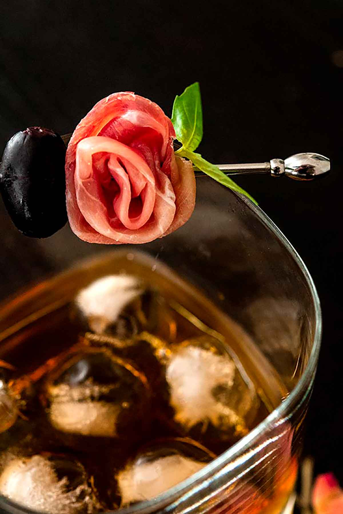 A prosciutto rose garnish on a glass filled with whisky and ice.