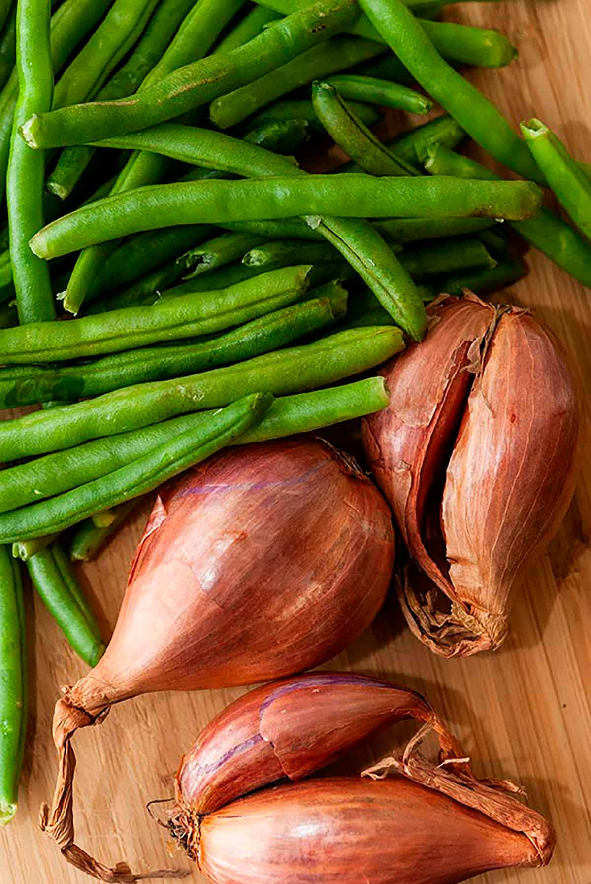 Uncooked shallots and green beans on a cutting board.