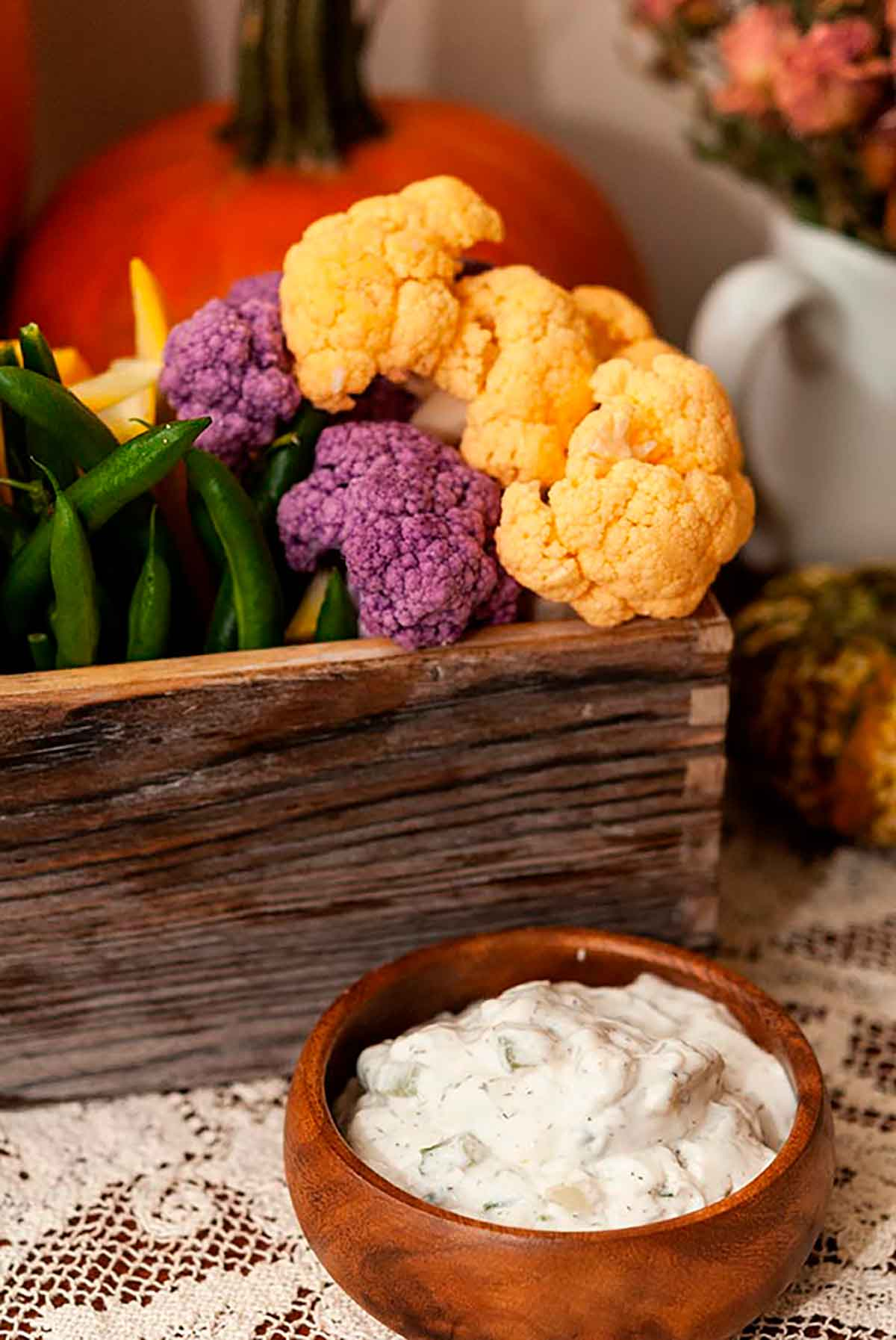 A small wooden bowl of vegetable dip in front of a flower box full of vegetables.