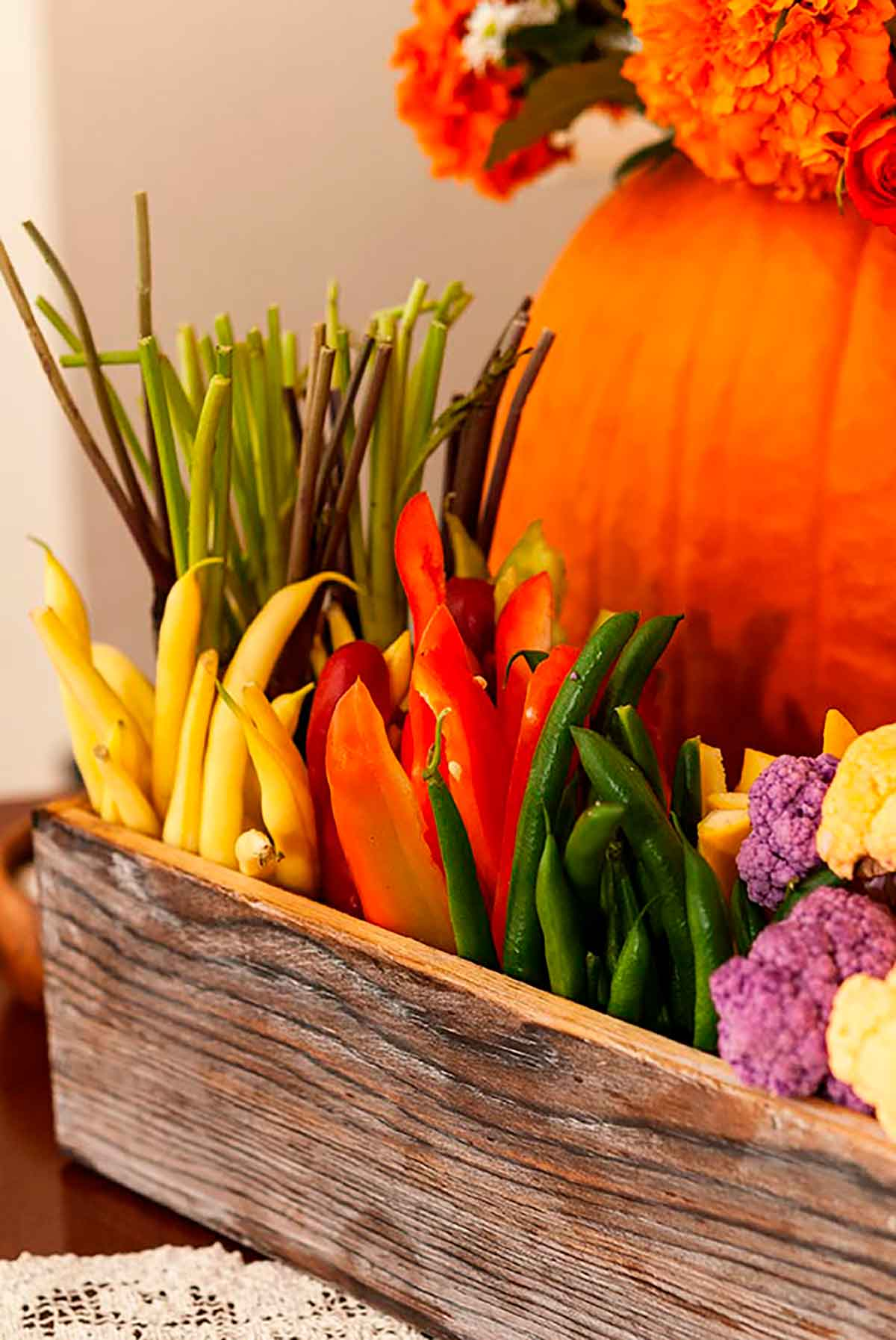 A flower box full of vegetables in front of a pumpkin.