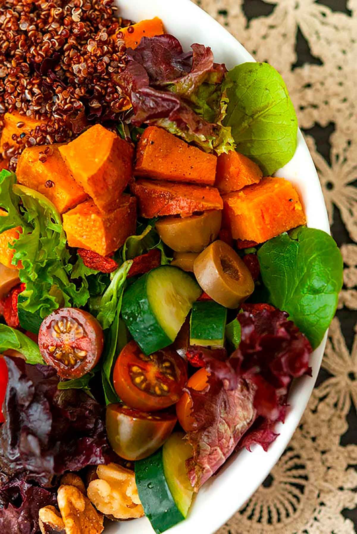 A colorful salad on a table with a lace tablecloth.