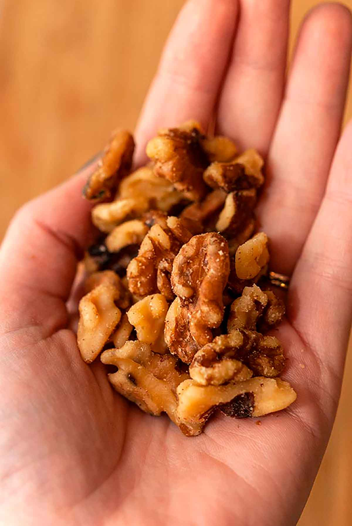 A hand holding walnuts.