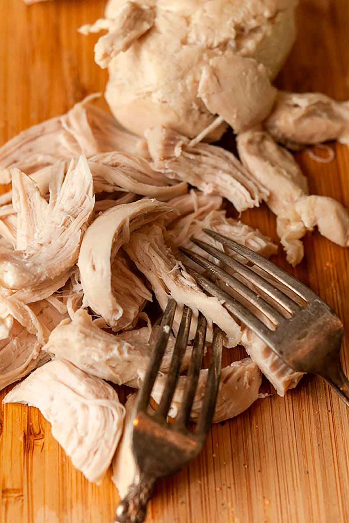 2 forks pulling apart cooked chicken on a cutting board.