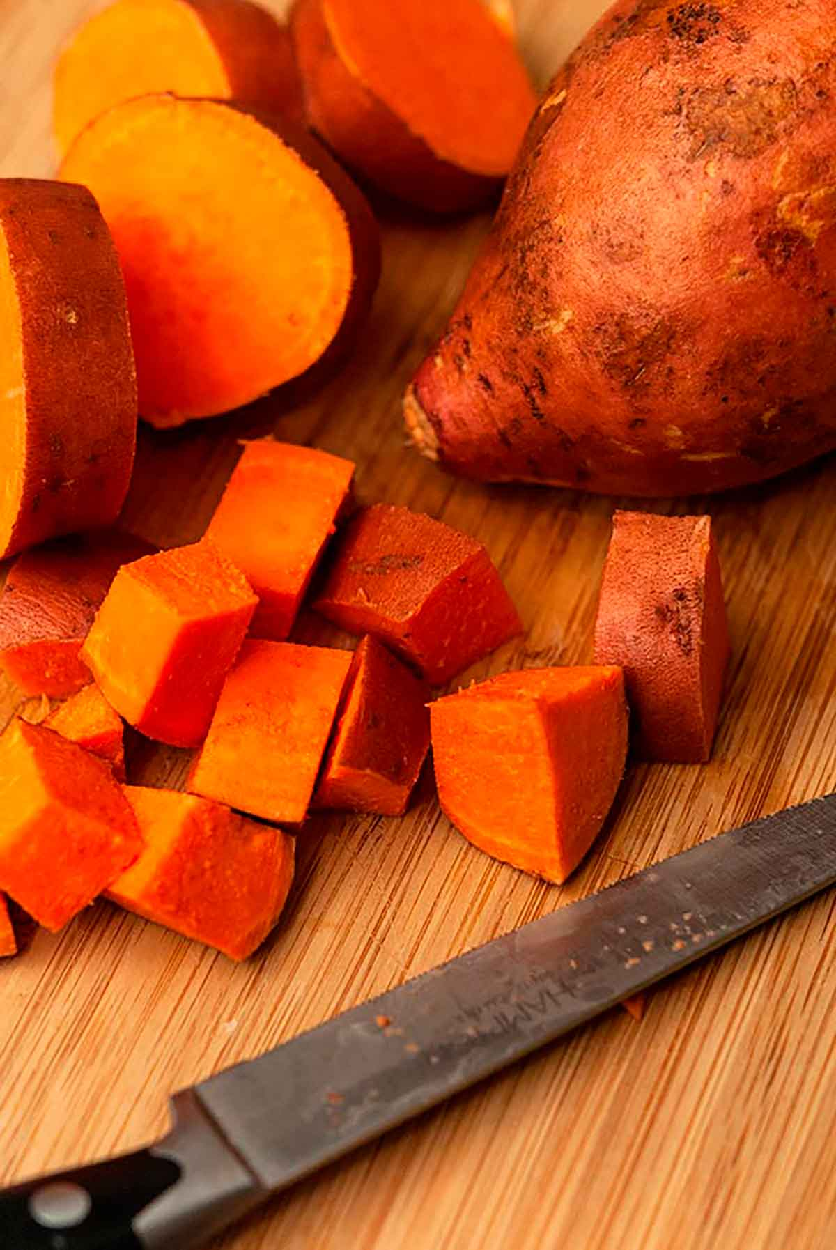 A diced sweet potato on a cutting board with a knife.