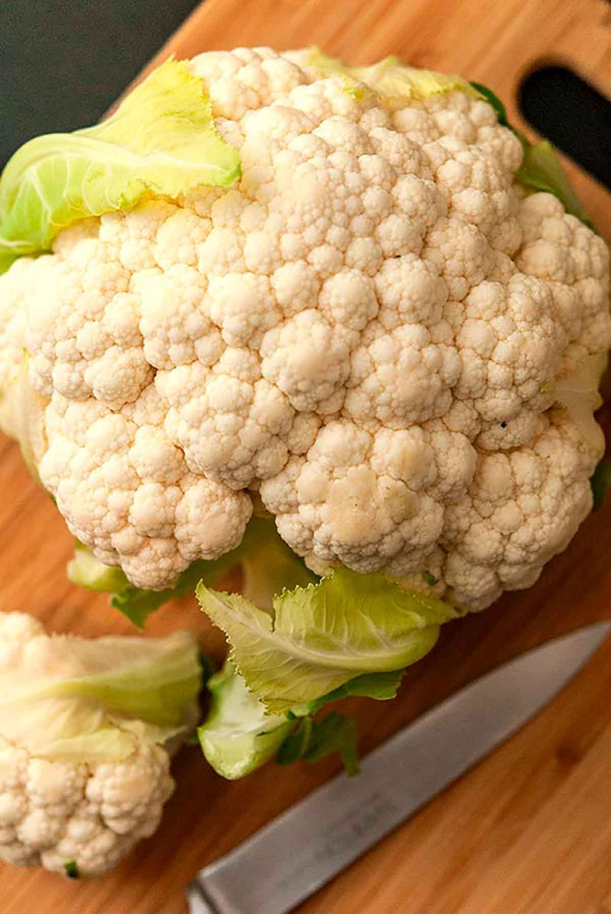 A close shot of a head of cauliflower on a cutting board beside a knife.