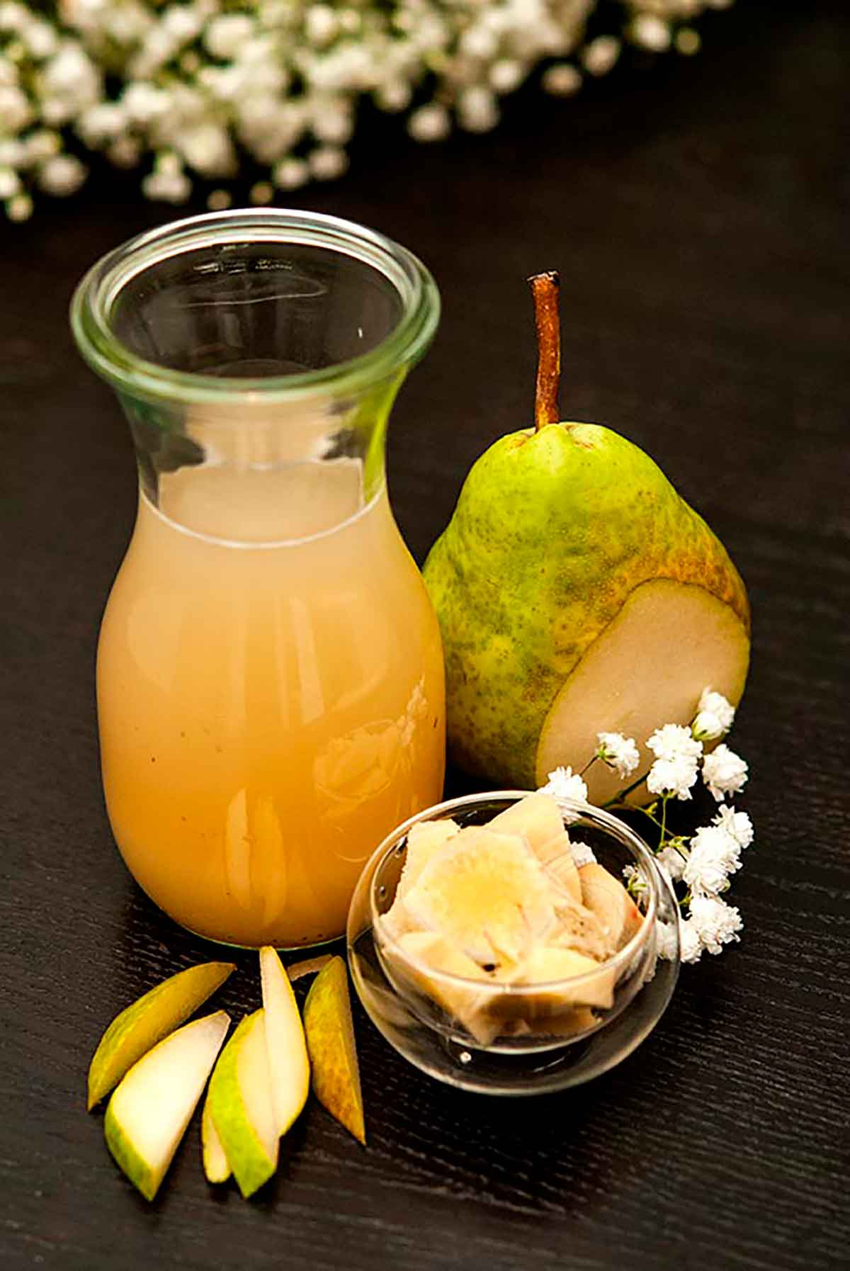 A small bottle of pear-ginger syrup on a table, along with a sliced pear, a small bowl of ginger and small pear slices.