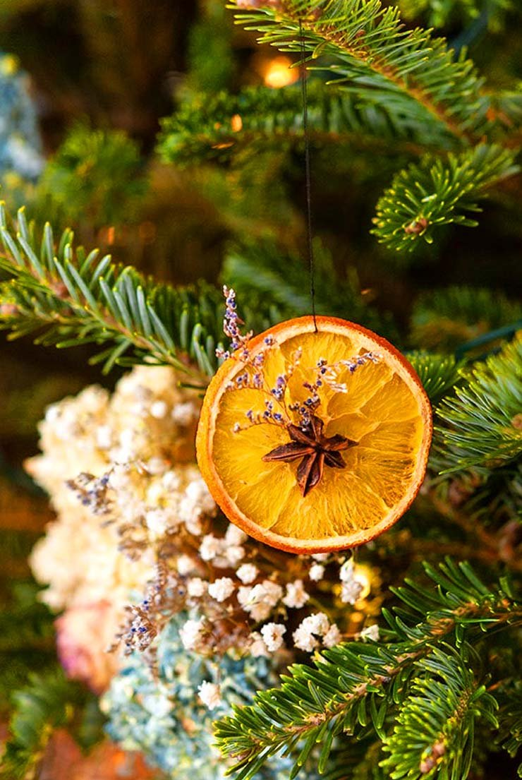 A Christmas decoration made from a dry orange and star anise, hanging on a Christmas tree.