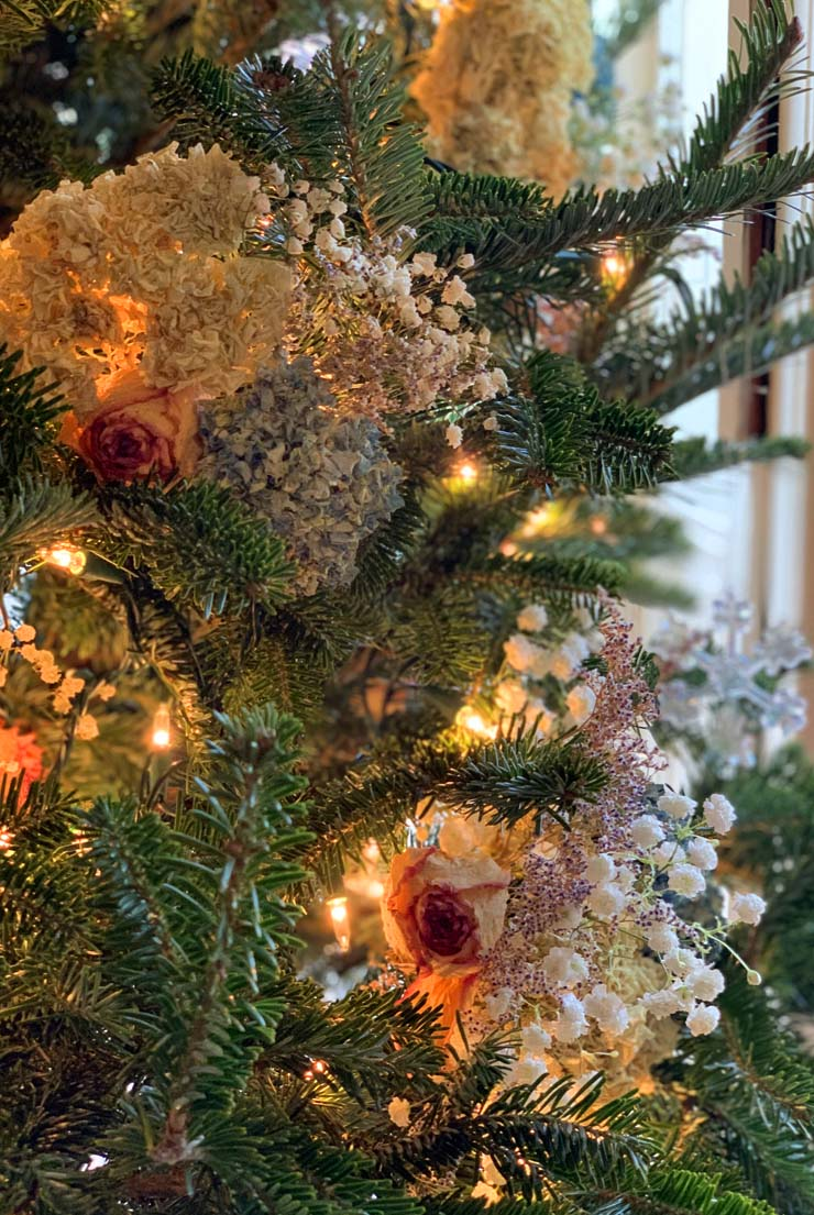 A Christmas tree with textural flower decorations and lights.