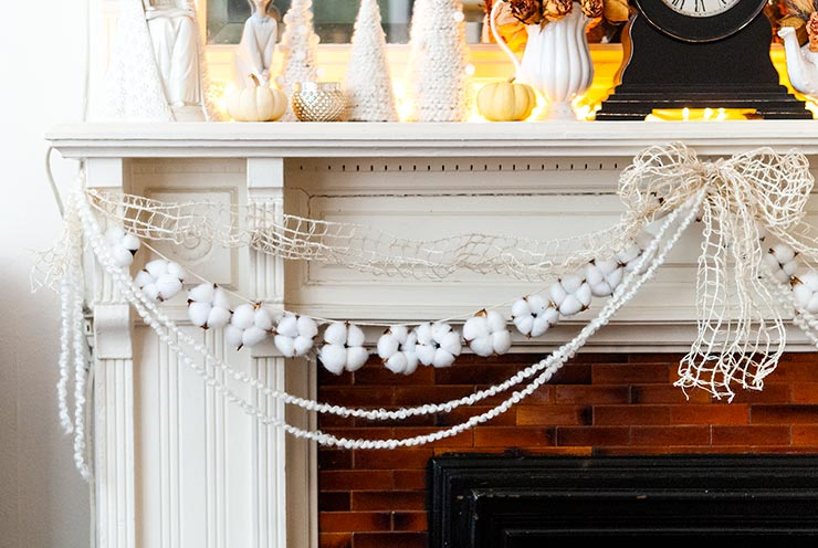 Cotton garland strung on a mantle with yarn and ribbon, with various Christmas decorations on the mantle top.
