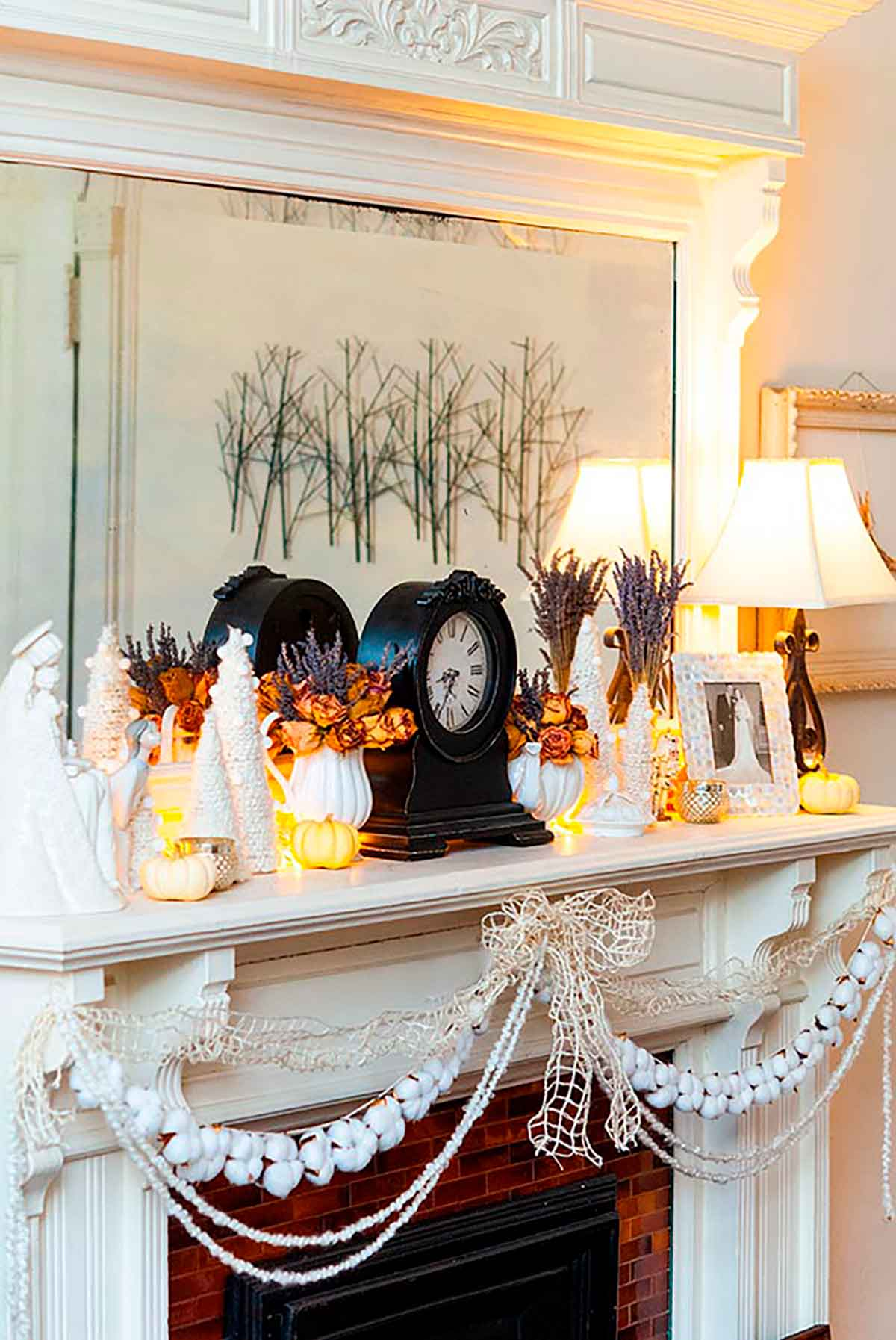 A mantle decorated with a clock, various Christmas decorations and cotton garland.