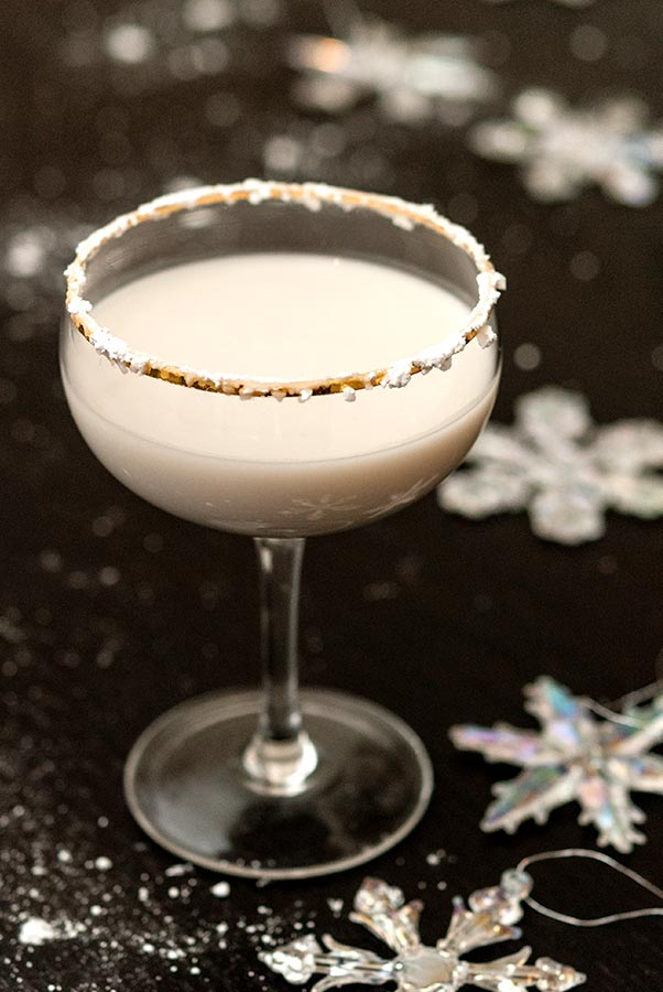 A white cocktail, rimmed with powdered sugar, on a black table, sprinkled with sugar and with a few snowflake ornaments.