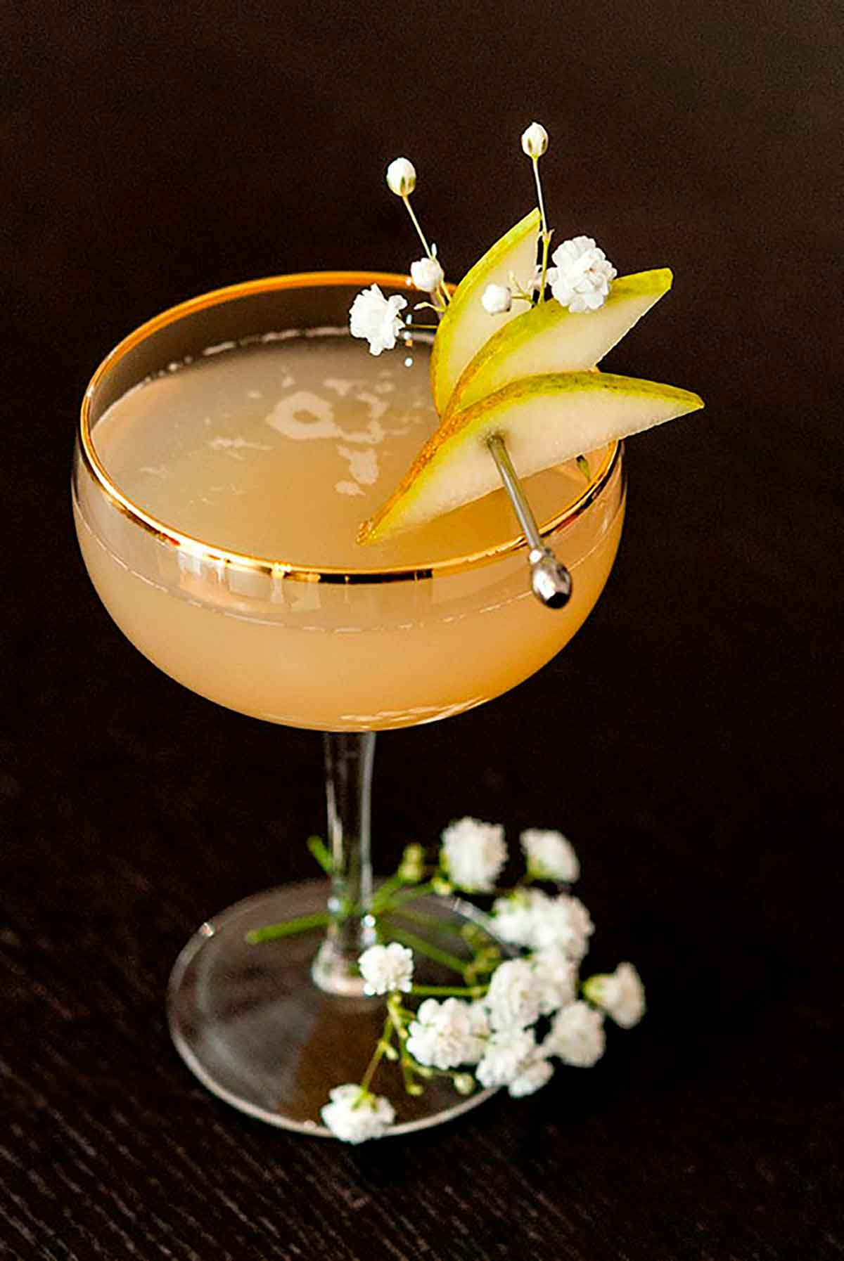 A pear and ginger cocktail, garnished with sliced pears on a cocktail pin and a few baby's breath flowers.