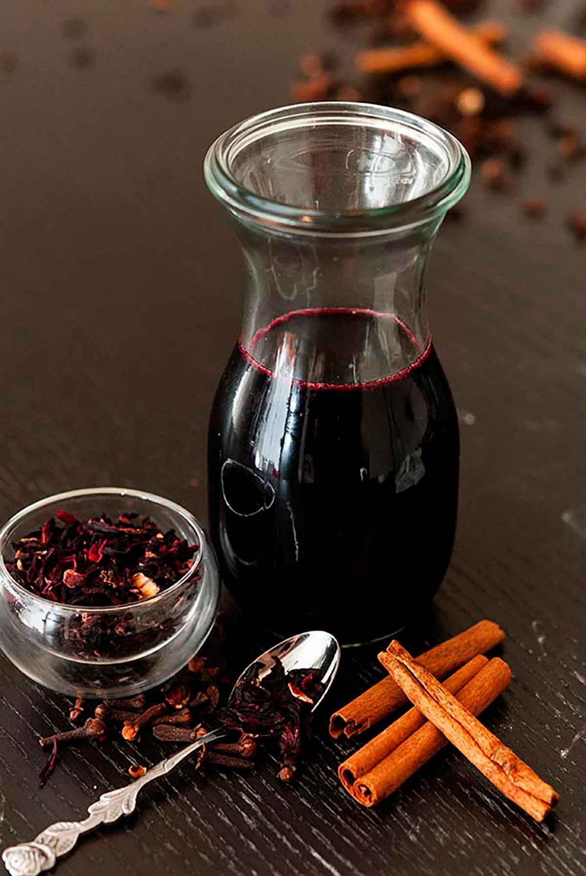 A bottle of spiced hibiscus syrup on a table surrounded by a few cinnamon sticks and a small bowl of hibiscus flowers.