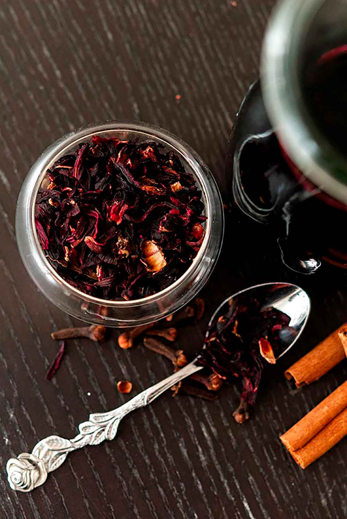 Dry hibiscus flowers in a small bowl next to a small spoon with a few scattered cloves, flowers and cinnamon sticks.
