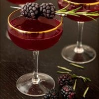 A cocktail on a table surrounded by a few scattered blackberries, and garnished with 2 frosted blackberries.