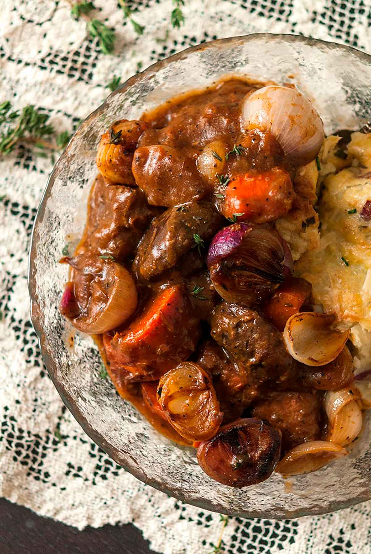 A bowl of beef bourguignon on a lace table cloth.