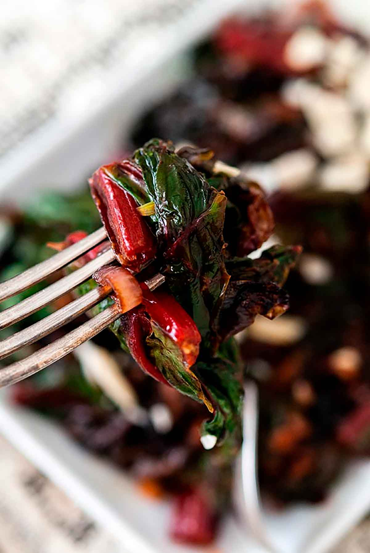A fork with sautéd Swiss chard and caramelized shallots above a bowl of Swiss chard.